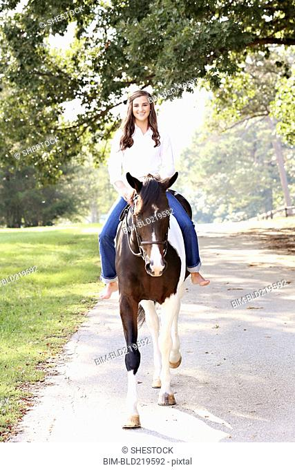 Woman riding horse on dirt road