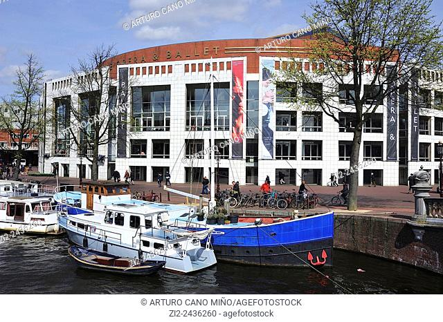 Dutch National Opera by Cees Dam and Wilhelm Holzbauer, 1986, is at riverside of Amstel. Amsterdam, Netherlands