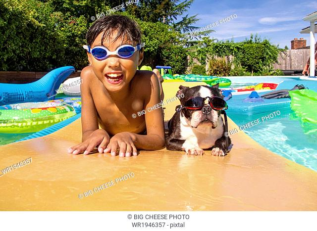 Boy and his Boston Terrier wearing matching goggles float on a toy in a pool