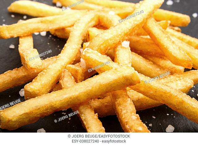 golden brown french fries with coarse salt on slate
