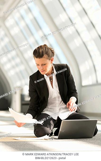 Caucasian businesswoman using laptop on lobby floor