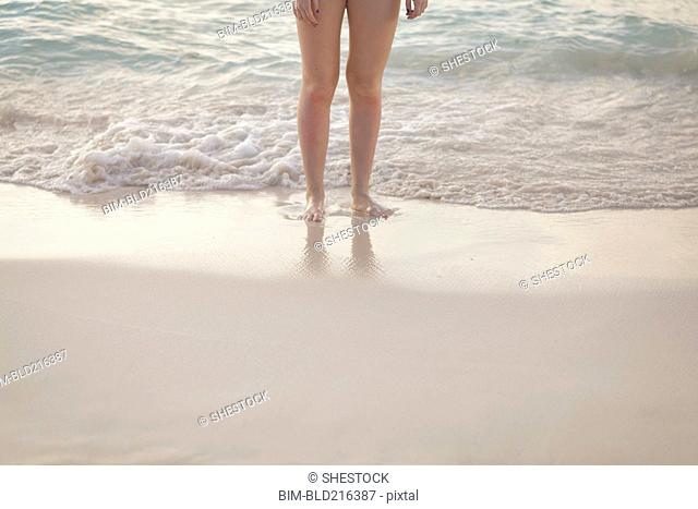 Caucasian girl standing in waves on beach