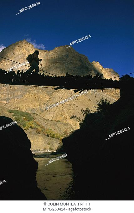 Trekker crossing Hanumar Bridge, near Zanskar River Gorge, Kingdom of Zanskar, Himalayas, northwest India
