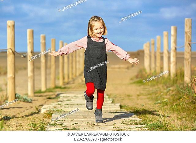 Girl walking on the beach, Zumaia, Gipuzkoa, Basque Country, Spain