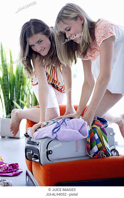 Teenage girls packing for vacation
