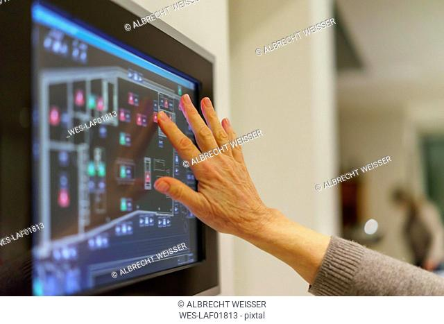 Senior woman's hand touching display panel of domestic technology