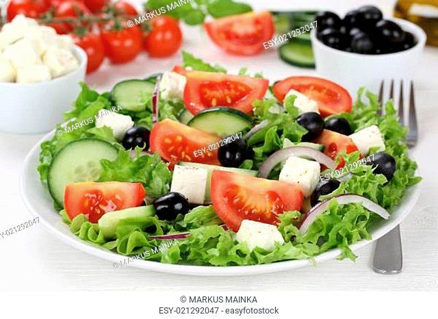 Griechischer Salat auf Teller, Tisch mit Tomaten, Feta Käse und Oliven