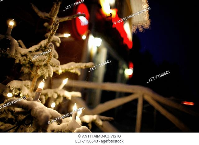 Electric candles are burning in a snowy Christmas tree in the yard of the hotel Hullu Poro at the Levi Ski Resort in Kittilä, Finnish Lapland