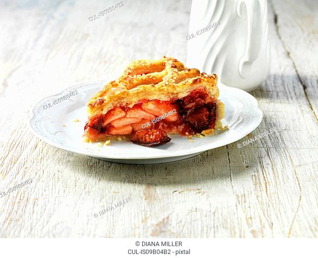Apple, plum and raspberry pie on white plate, white jug, white washed wooden table