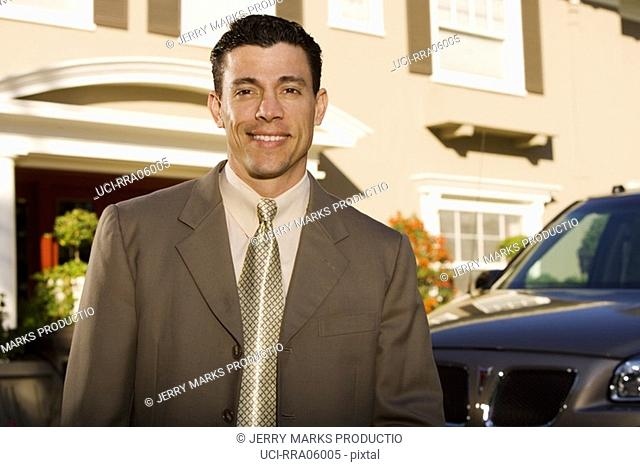 Businessman standing outside his house with vehicle