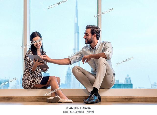 Businesswoman and man sitting at window, Dubai, United Arab Emirates