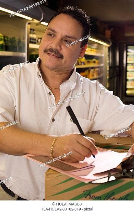 Small businessman taking inventory of groceries