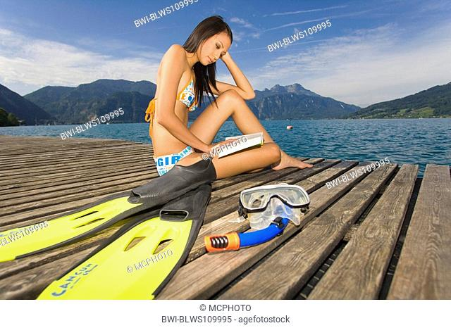 young woman with bikini sits on a boardwalk reading in a book, Austria, Attersee