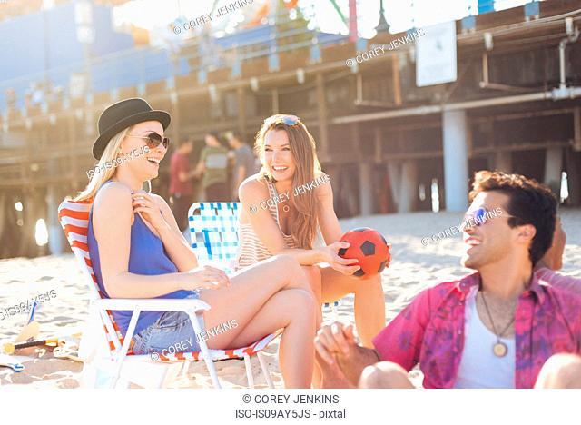 Three adult friends chatting on beach, Santa Monica, California, USA