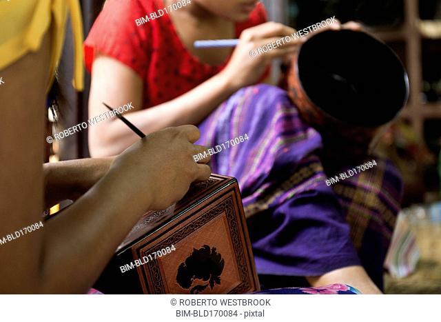 Asian artisans carving traditional design in workshop