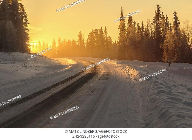 Winter landscape in direct light with road leading in to the light, fog and mist over the road, Gällivare, Swedish Lapland, Sweden