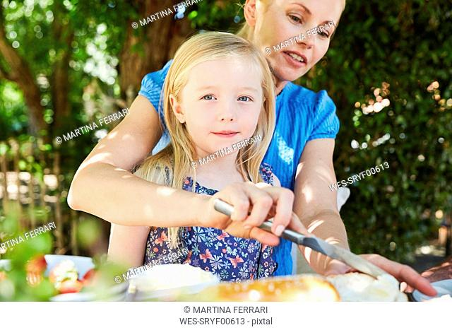 Girl with mother having breakfast at garden table