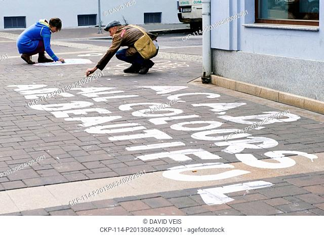 Activists write anti racist slogans to protest on the street against the Anti Romany march of right wing extremists in Ceske Budejovice