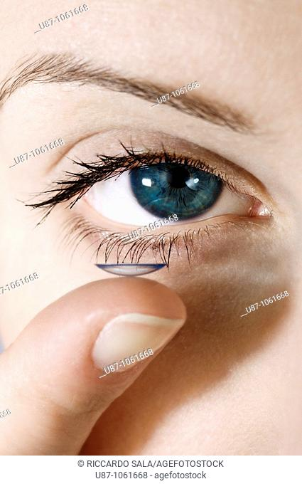 A facial close up of a young woman putting a contact lens onto his eye