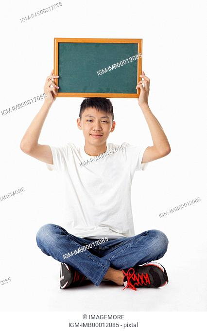 Teenage boy holding blackboard and smiling at the camera