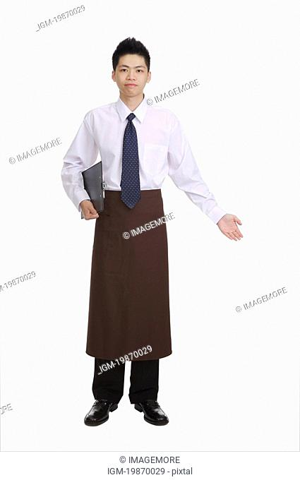 Young waiter gesturing welcome and holding a menu