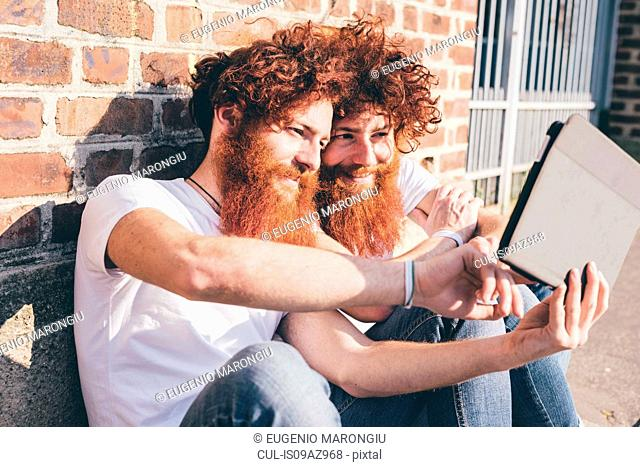 Young male hipster twins with red hair and beards browsing digital tablet on sidewalk