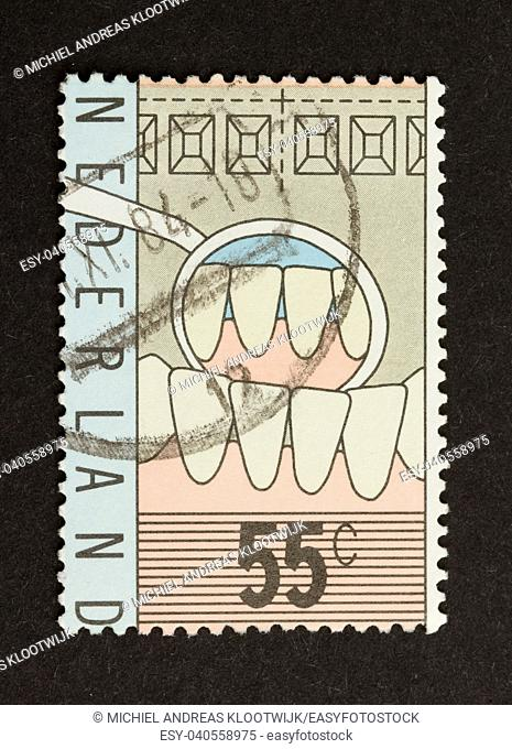 HOLLAND - CIRCA 1980: Stamp printed in the Netherlands shows the work of a dentist, circa 1980