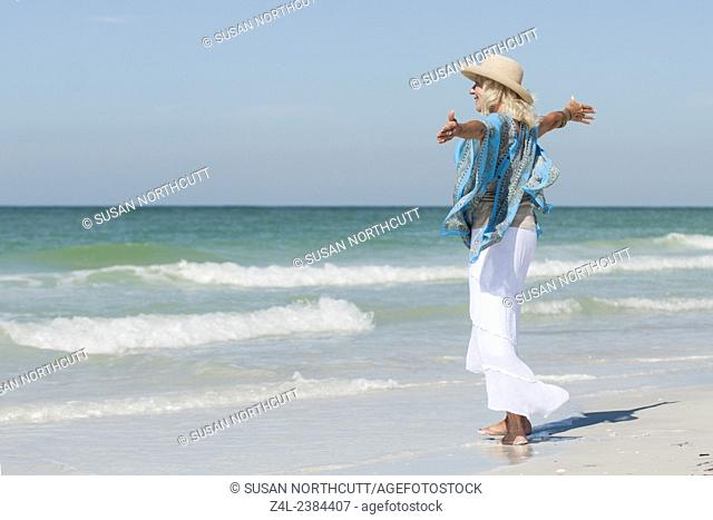 Mature woman standing on Coquina Beach looking out to sea, Anna Maria Island, Florida. she is smiling and has her arms open wide