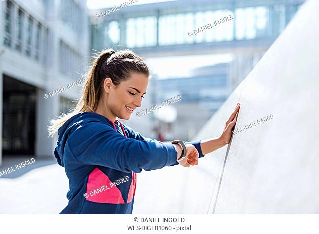 Smiling young woman having a break from exercising looking on smartwatch