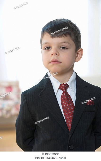 Mixed race boy playing businessman