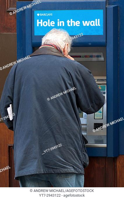 "People using local cash Barclays """"Hole in the Wall"""" cash machine, England, UK"