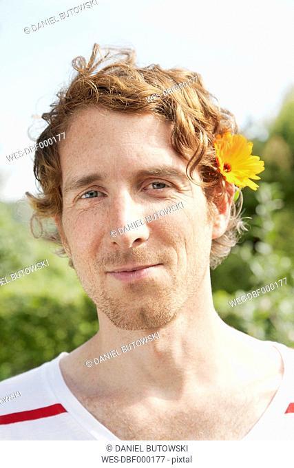 Germany, Hamburg, Man wearing marigold in allotment garden
