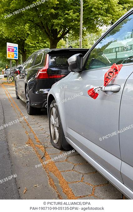 10 July 2019, Hamburg: A Volvo and a Skoda passenger car stand with flat tyres and with a police barrier tape attached to the door handles on the parking strip...