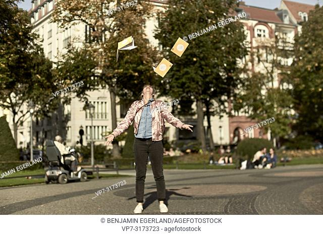 Woman throwing city guide maps in the air, in Berlin, Germany