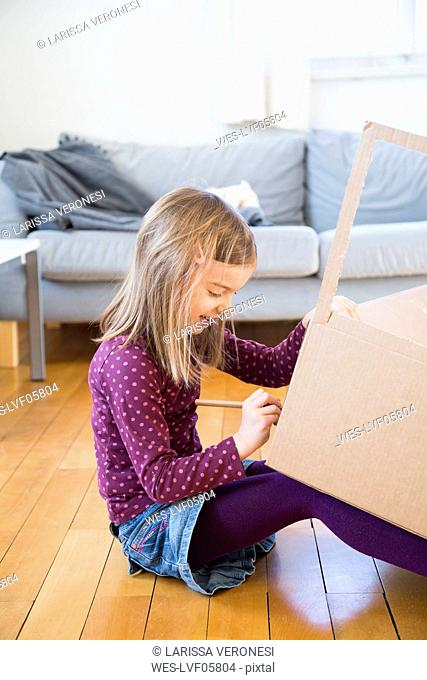 Girl tinkering with cardboard box at home