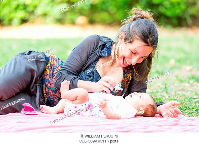 Mother lying on side on blanket teasing a by girl with pacifier