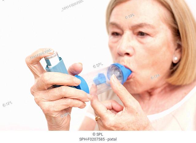 Senior woman using an inhaler