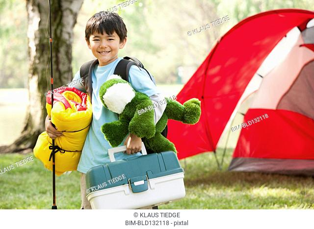Asian boy carrying camping gear