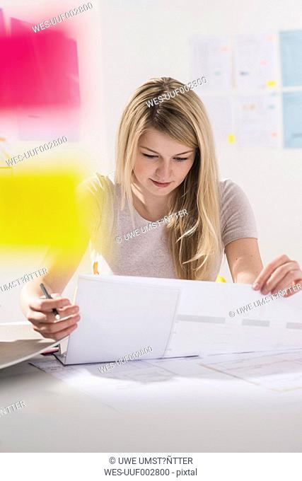 Young woman at desk looking at documents