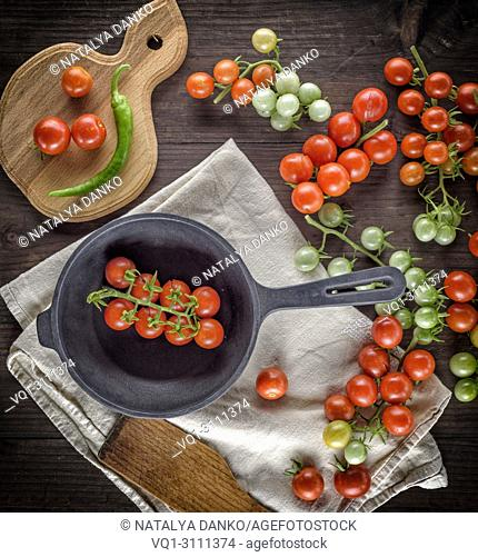 black cast iron round frying pan and ripe red cherry tomatoes on a brown wooden table, top view
