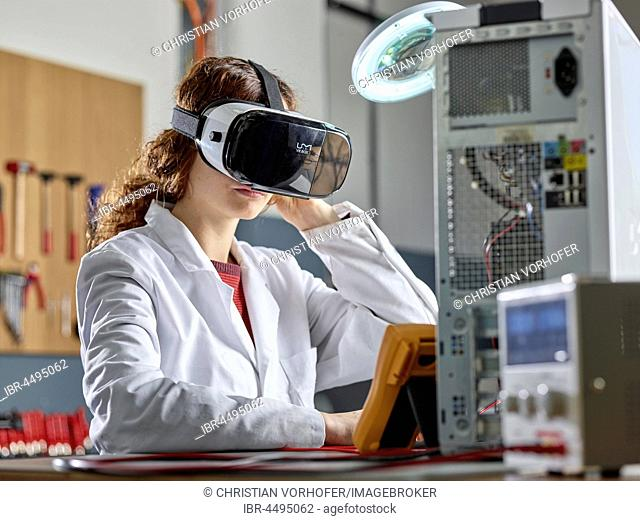 Woman with VR goggles and lab coat sitting in front of PC open in an electronics laboratory, Austria