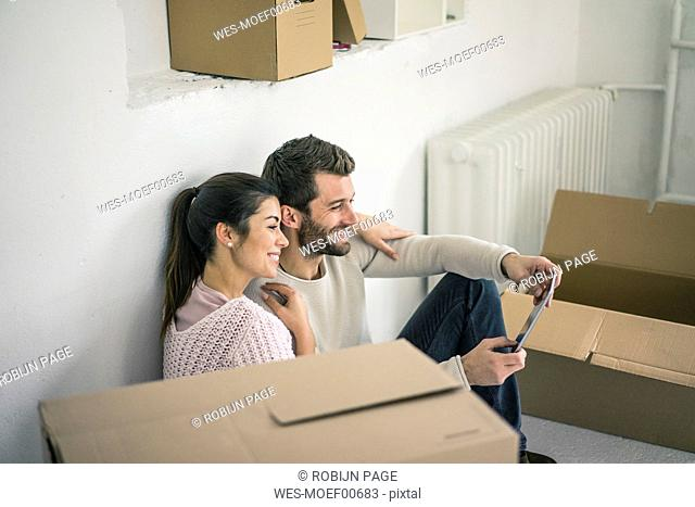 Couple sitting in new home surrounded by cardboard boxes looking at tablet