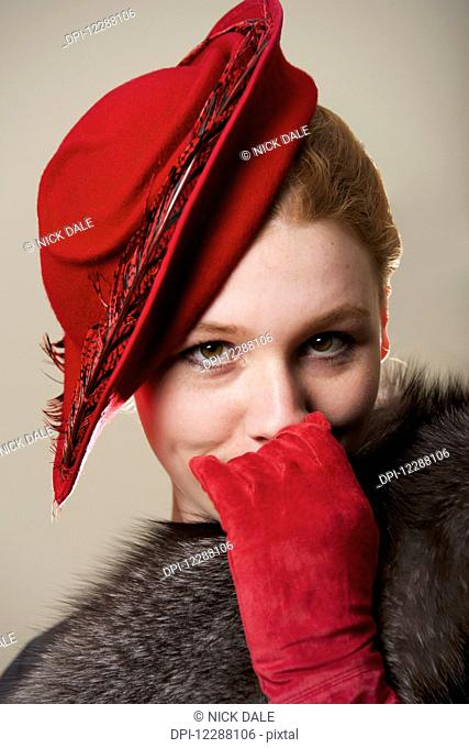 Portrait of a young woman with red hair wearing a red hat, red suede gloves and grey fur coat; Caldecott, England