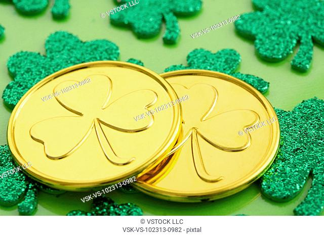 Close up of gold coins with shamrock pattern and shamrock below