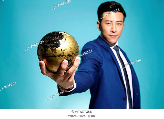 Young business man holding the globe