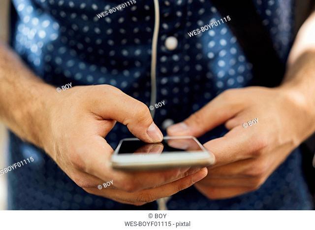 Man' hands using smartphone, close-up