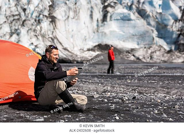 Middle aged man sitting next to a tent and reading from a tablet on the moraine beach of Shoup glacier with a woman in back ground, Shoup Bay State Marine Park
