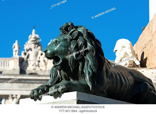 Madrid, Spain. One of the bronze Lions at Plaza de Oriente with Palacio Real, or Royal Palace background