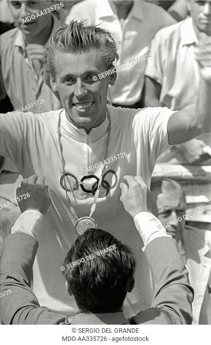Vicotr Kapitonov rejoicing over the Olympic gold medal. A man presenting the gold medal to Victor Kapitonov, the Soviet cyclist who won the gold medal on the...