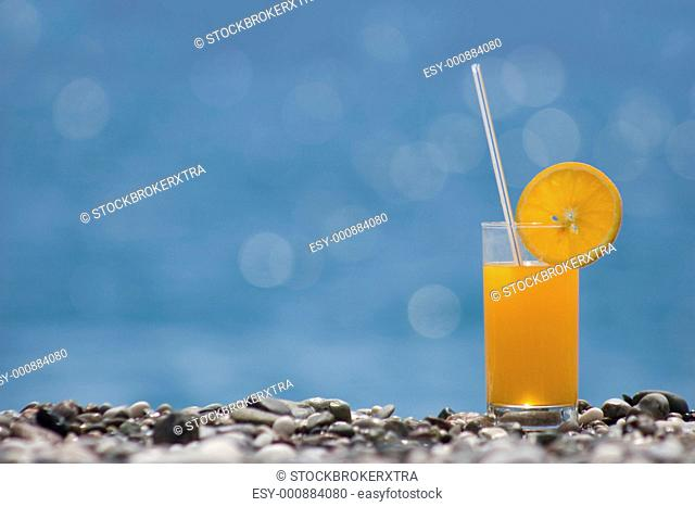 Close-up of orange juice on river pebbles at background of blurred water